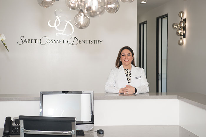 Dr. Shohreh Sabeti poses in front of Sabeti Cosmetic Dentistry's office sign.
